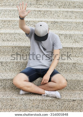 Portrait of teenage boy showing hand at the camera.Teenager covering his eyes with cap - stock photo