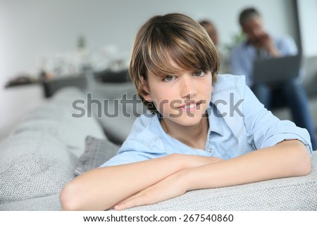 Portrait of teenage boy sitting in sofa, parents in background