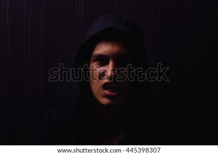 Portrait of teenage boy with serious expression and black hoodie on his head, brown dark hair, direct gaze, yells at the camera. Dark background, lights and shadows