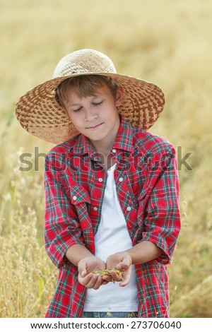 Portrait of teenage farmer boy is checking golden yellow oat seeds in cupped palms at harvest time field - stock photo