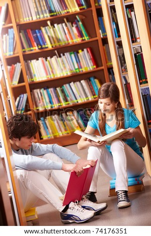 Portrait of teenage friends reading books in library - stock photo