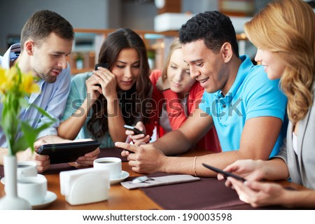 Portrait of teenage friends using modern gadgets while sitting in cafe