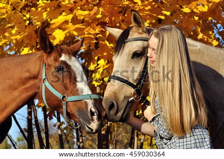 portrait of teenage girl and horses in autumn day