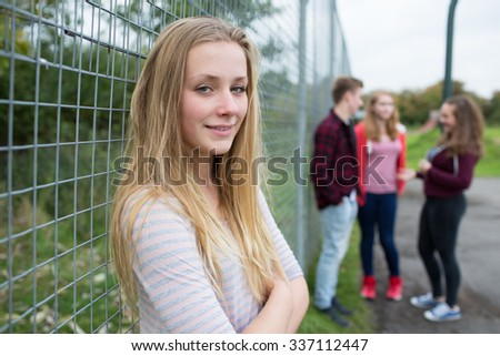 Portrait Of Teenage Girl Hanging Out With Friends In Playground