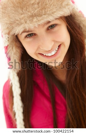 Portrait Of Teenage Girl In Snow Wearing Fur Hat - stock photo