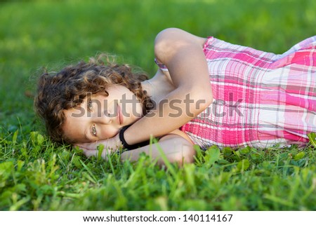 Portrait of teenage girl lying on grass at park