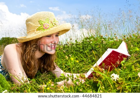 Portrait of teenage girl reading book in summer meadow with straw hat