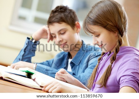 Portrait of teenage girl reading book with her classmate at background - stock photo