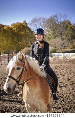 Portrait of teenage girl riding horse outdoors on sunny autumn day - stock photo
