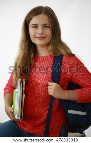 Portrait of teenage girl with backpack and notebooks on white background. Back to school.