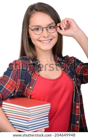 Portrait of teenage girl with glasses holding books, isolated on white background - stock photo