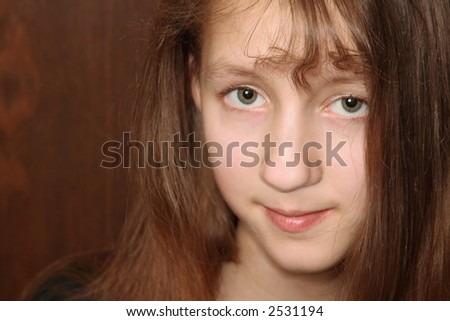 Portrait of teenage girl with long hair against dark brown background