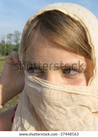 Portrait of teenage girl with scarf over the face - stock photo