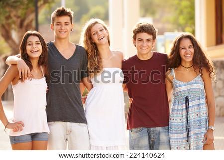 Portrait Of Teenage Group Walking Along Street - stock photo