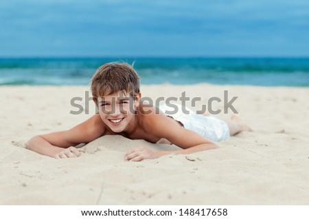 Portrait of teenage lying on sand near sea - stock photo