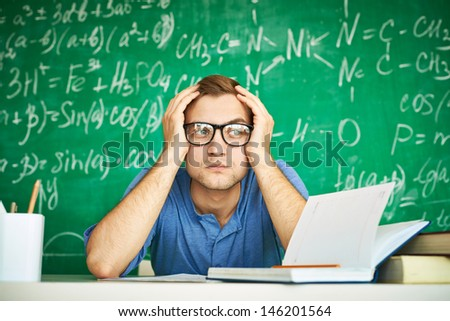 Portrait of teenage student touching his head while carrying out graduation test on background of chalkboard