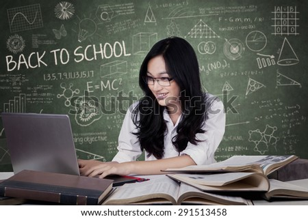 Portrait of teenage student with black hair studying in the class while using a laptop - stock photo