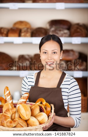 Portrait of teenage waitress holding bread basket in coffee shop - stock photo