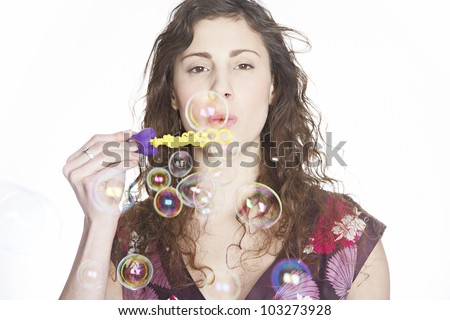 Portrait of teenager blowing bubbles towards the camera.