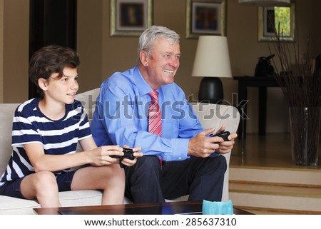Portrait of teenager boy sitting at sofa at home with his grandfather holding hands controller and playing online.  - stock photo