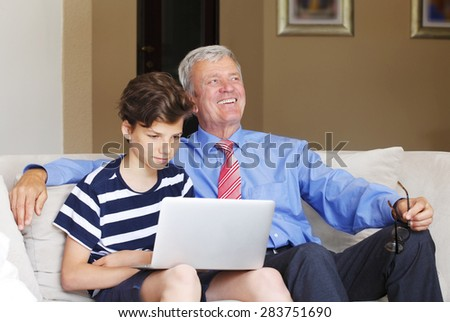 Portrait of teenager boy sitting at sofa with his happy grandfather and using laptop.  - stock photo