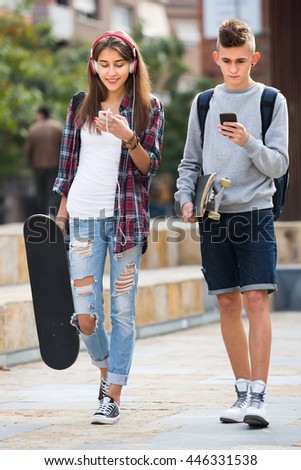 Portrait of teenager couple walking with skateboards and smartphones outdoors 