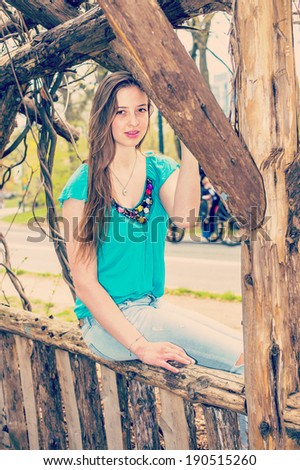 Portrait of Teenager.  Dressing in a blue sleeveless top, fashionable jeans, a beautiful teenage girl is sitting on a wooden fence, charmingly looking at you. Instagram Nashville effect. - stock photo