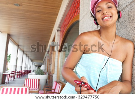 Portrait of teenager girl at colorful bar on a summer day, using headphones to enjoy listening to music, joyful expression. African american fun and technology retro adolescent lifestyle, outdoors. - stock photo