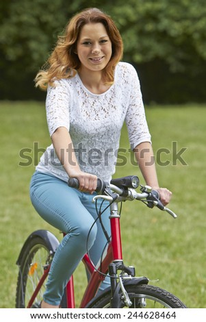 Portrait Of Teenager Girl Riding Bike In Countryside