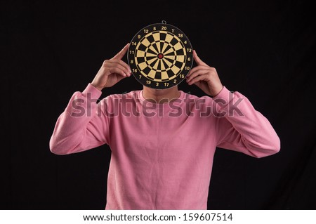 Portrait of teenager holding a dartboard over his face - stock photo