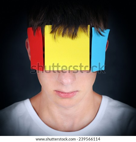 Portrait of Teenager on the dark background with Colored Paper on a Face - stock photo
