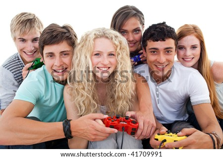 Portrait of teenagers having fun playing video games in the living-room - stock photo