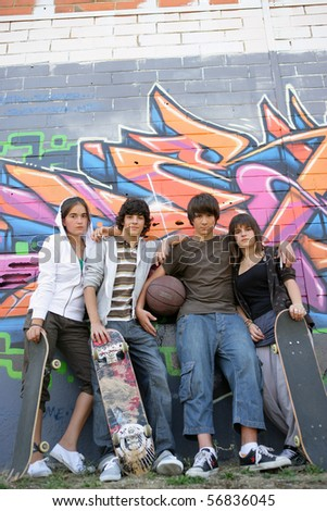 Portrait of teenagers leaning on a wall of graffiti - stock photo