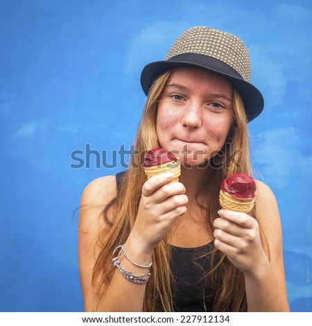 Portrait of teengirl with ice cream, blue wall background (Instagram style series) - stock photo