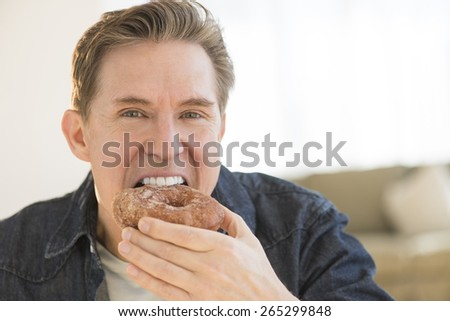 Portrait of tempted mature man having donut at home - stock photo