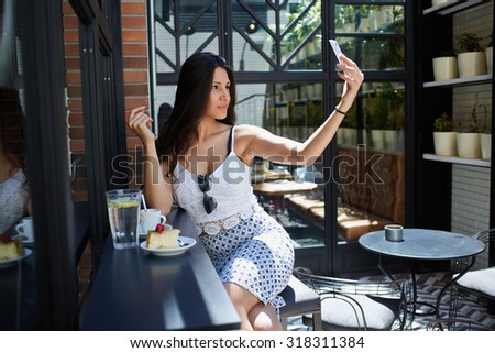Portrait of tempting latin woman with sexy figure taking self picture with cell cellphone while sitting on terrace of modern coffee shop,young female tourist making self photo during vacation holidays - stock photo