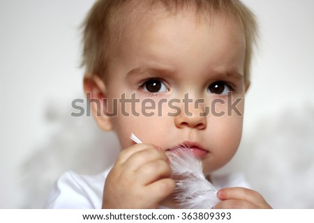 Portrait of tender blond toddler in a white t-shirt touching himself with white feather over white background, romantic and love concept