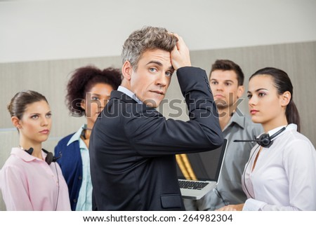 Portrait of tensed manager in meeting with team at call center