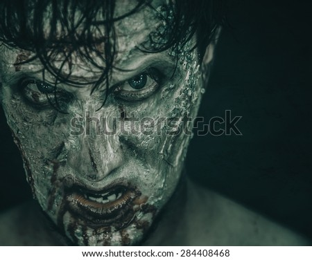 Portrait of terrible zombie man in blood, Halloween or horror theme. Space for text in right part of the image - stock photo