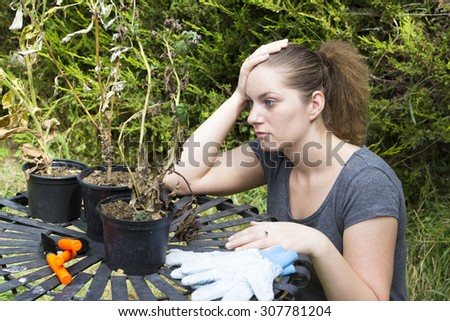 Portrait of terrified girl with shrunken plants in backyard - stock photo