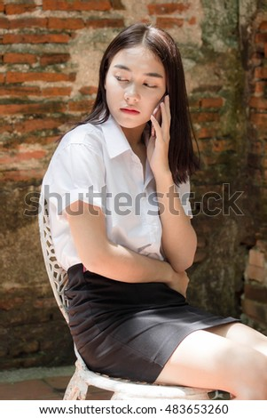 Portrait of thai adult student university beautiful girl calling smart phone