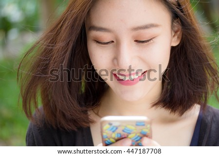 Portrait of thai adult student university beautiful girl using her smart phone - stock photo