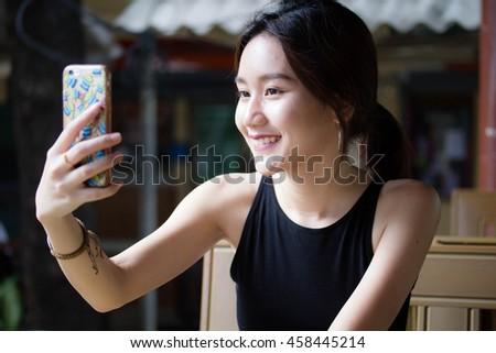 stock photo portrait of thai adult student university beautiful girl using her smart phone selfie 458445214