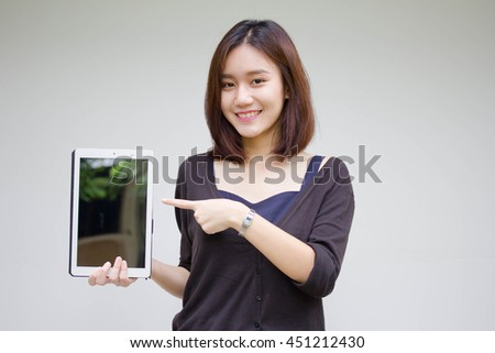 Portrait of thai adult student university beautiful girl using her tablet. - stock photo