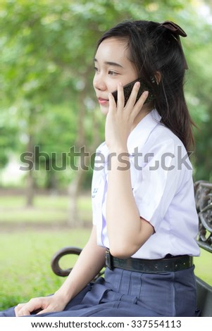 Portrait of thai student teen beautiful girl Answer the phone and smile.