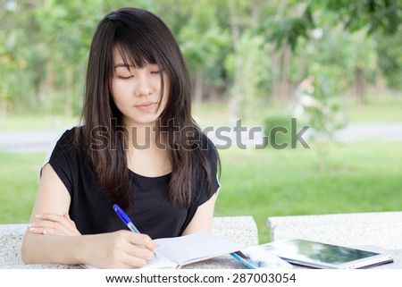 Portrait of thai student teen beautiful girl write a book sitting in park. - stock photo