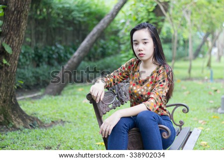 Portrait of thai teen beautiful girl relax and smile in park.
