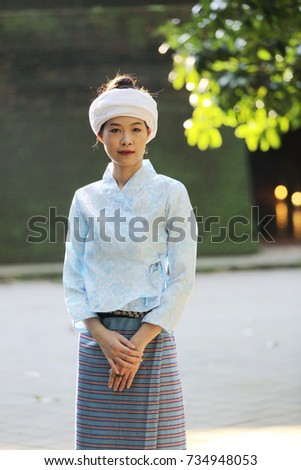 Portrait of thai young woman with traditional thai dress in thai temple with tree and sunrise
