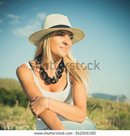 portrait of the attractive, slender, beautiful young Caucasian  blonde girl in a jeans jacket. Smiling girl enjoys fine warm summer weather. Photo with instagram style filters - stock photo