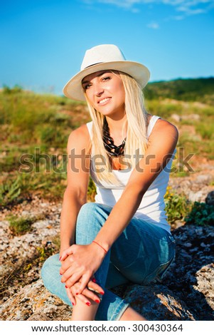 portrait of the attractive, slender, beautiful young Caucasian  blonde girl in a stinny hat. Smiling girl enjoys fine warm sunner weather highly in mountains.  - stock photo